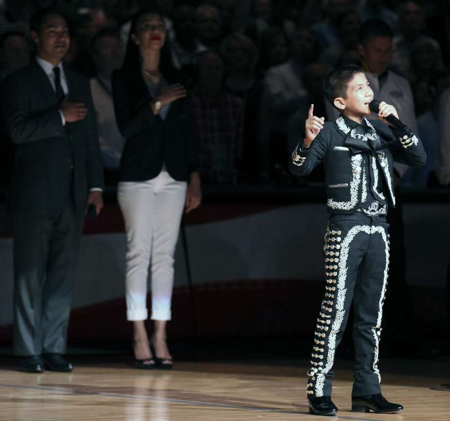 Sebastien De La Cruz sings the national anthem before the start of Game 4 of the NBA Finals at the AT&T Center on Thursday, June 13, 2013. Behind him are San Antonio's mayor Julian Castro and his wife. (Kin Man Hui/San Antonio Express-News)