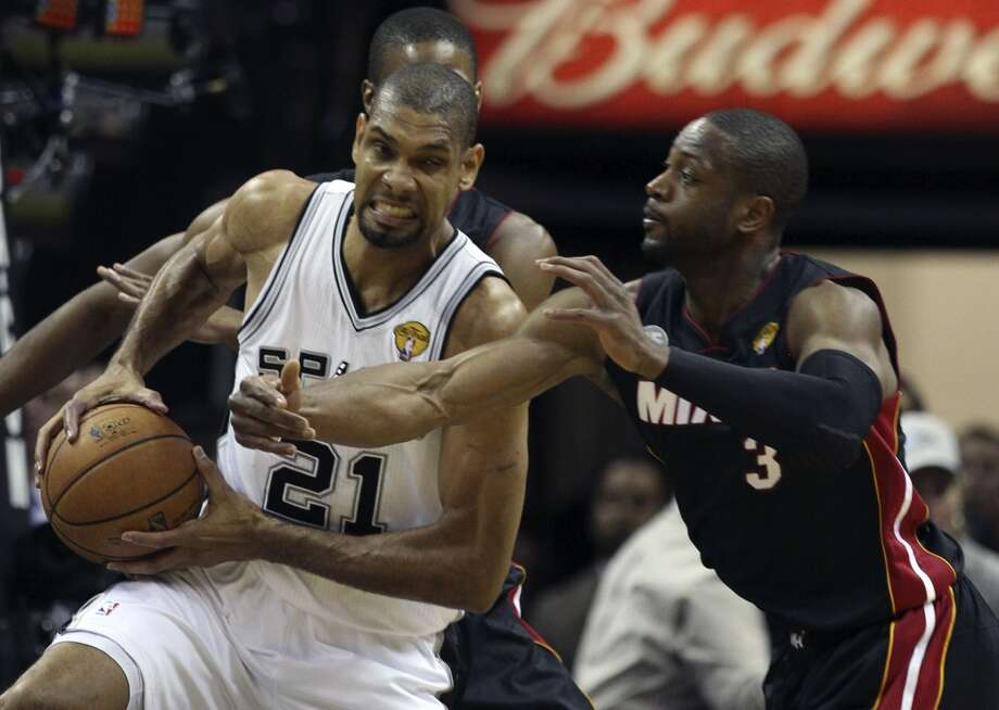 San Antonio Spurs' Tim Duncan brags a rebound while under pressure from Miami Heat's Dwyane Wade during the first half of Game 4 of the NBA Finals at the AT&T Center on Thursday, June 13, 2013. (Kin Man Hui/San Antonio Express-News)