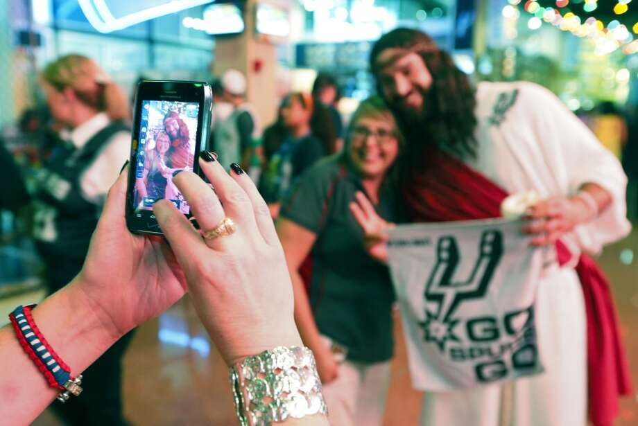 A man known as the Spurs Jesus, who wouldn't give his name, has his picture taken before the start of Game 4 of the 2013 NBA Finals Thursday June 13, 2013 at the AT&T Center. (Edward A. Ornelas/San Antonio Express-News)