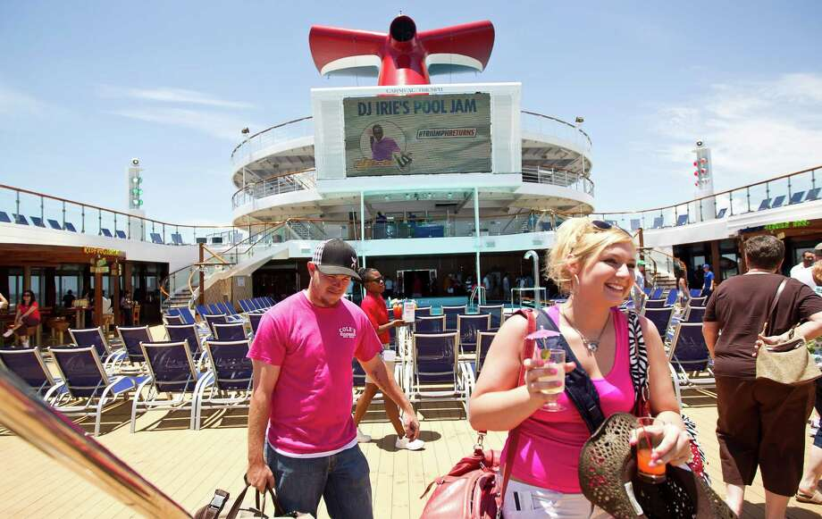 Shelby Gilson, front, and Roy Evans, both of Hico, Texas, walk across the pool deck to check into their room as they board the Carnival Triumph cruise ship, Thursday, June 13, 2013, at the Port of Galveston in Galveston. Photo: Nick De La Torre, Houston Chronicle / © 2013  Houston Chronicle