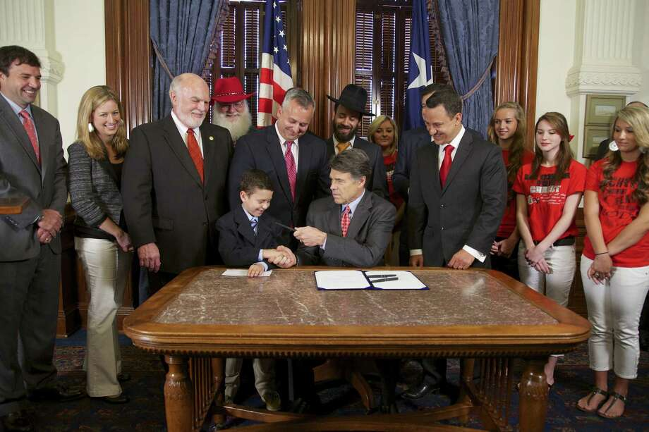 "Eight-year-old Reagan Bohac congratulates Gov. Rick Perry on signing the ""Merry Christmas bill"" into law. Photo: Courtesy Photo / Office Of The Governor"