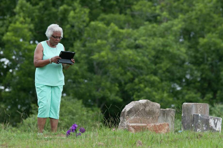 Mable Huff York uses her tablet to photograph graves in the cemetery in order to record them at the Fort Bend County Heritage Unlimited Museum, in Kendleton, Wednesday, June 12th, 2013. (Jamaal Ellis / For the Houston Chronicle) Photo: Jamaal Ellis, For The Chronicle / ©2013 Houston Chronicle