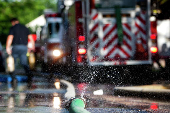 Water sprays from a hose as the Houston Fire Department crews battled a blaze that erupted about 6:50 a.m. at an apartment complex on Upland near Sherwood Forest Thursday, June 13, 2013, in Houston. The 1.11 fire tore through the apartment, but, left no injuries.