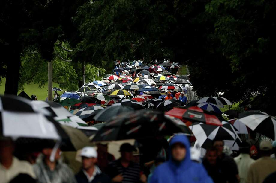 ARDMORE, PA - JUNE 13:  Patrons walk off the course after play was suspended due to weather during Round One of the 113th U.S. Open at Merion Golf Club on June 13, 2013 in Ardmore, Pennsylvania. Photo: Rob Carr, Getty Images / 2013 Getty Images