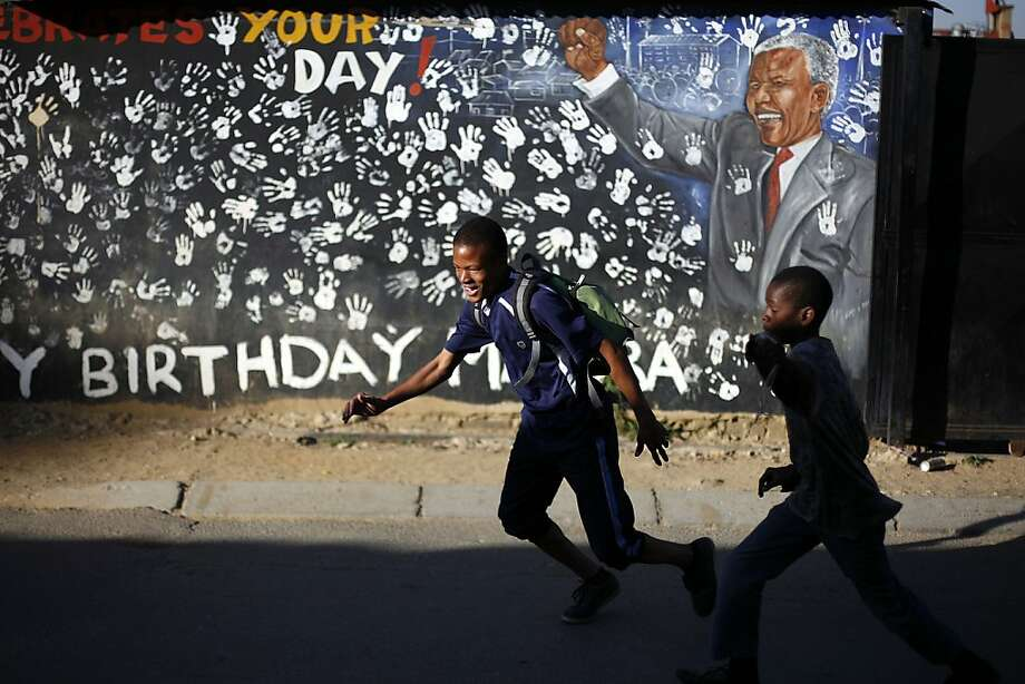 School pupils walk in front of a year old mural outside former South African President Nelson Mandela's former Alexandra township residence in Johannesburg, South Africa, Thursday June 13, 2013. Nelson Mandela remained hospitalized for the sixth day with an occurring lung infection. The latest government report says that he remains in a serious but stable condition. (AP Photo/Jerome Delay) Photo: Jerome Delay, Associated Press