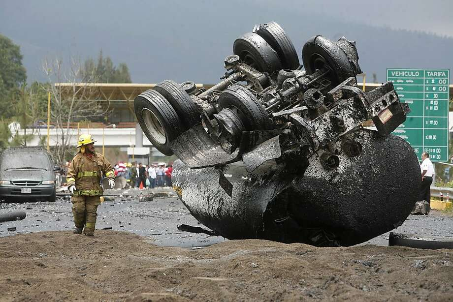 A firefighter stands next a flipped over truck that was carrying tar on a highway just west of the state capital city of Morelia, Mexico, Thursday, June 13, 2013. Authorities say the tanker truck carrying tar slammed into a highway toll booth that had temporarily been taken over by protesting teachers. They say seven people are dead and another 14 injured. Most of the dead and injured are believed to be teachers who have been holding a series of protests in the western state of Michoacan. The teachers are protesting educational reforms that would reduce union power in hiring decisions and establish teacher evaluations. (AP Photo/Gustavo Aguado) Photo: Gustavo Aguado, Associated Press