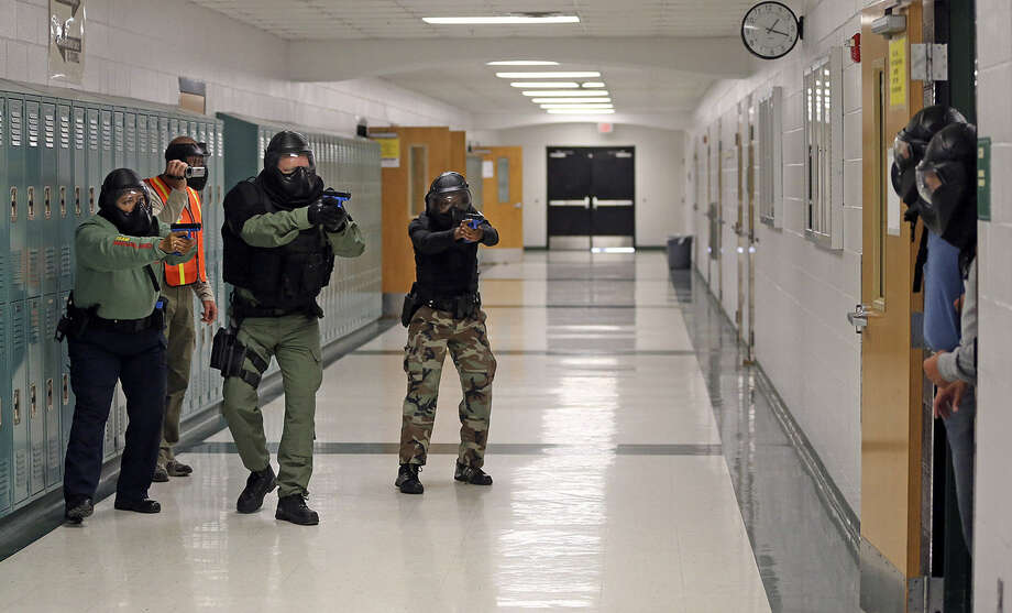 Officers move in on a crisis situation in a classroom as police are trained in how to respond to a school shooting as the Advanced Law Enforcement Rapid Response Training program is held at MacArthur High. Photo: Tom Reel / San Antonio Express-News
