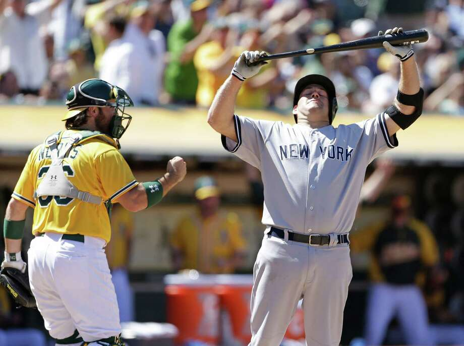 New York Yankees' Kevin Youkilis, right, reacts after striking out with the bases loaded against Oakland Athletics relief pitcher Jerry Blevins in the 11th inning of their baseball game on Thursday, June 13, 2013, in Oakland, Calif. Athletics catcher Derek Norris, left, reacts. (AP Photo/Eric Risberg) Photo: Eric Risberg