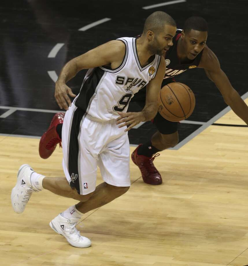 San Antonio Spurs' Tony Parker and Miami Heat's Mario Chalmers run for a loose ball during the first half of Game 4 of the NBA Finals at the AT&T Center on Thur., June 13, 2013. (Jerry Lara/San Antonio Express-News)
