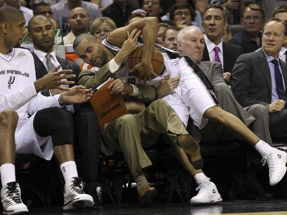 San Antonio Spurs' Tony Parker falls into his coaches including coach Gregg Popovich during the first half of Game 4 of the NBA Finals at the AT&T Center on Thursday, June 13, 2013. (Kin Man Hui/San Antonio Express-News)