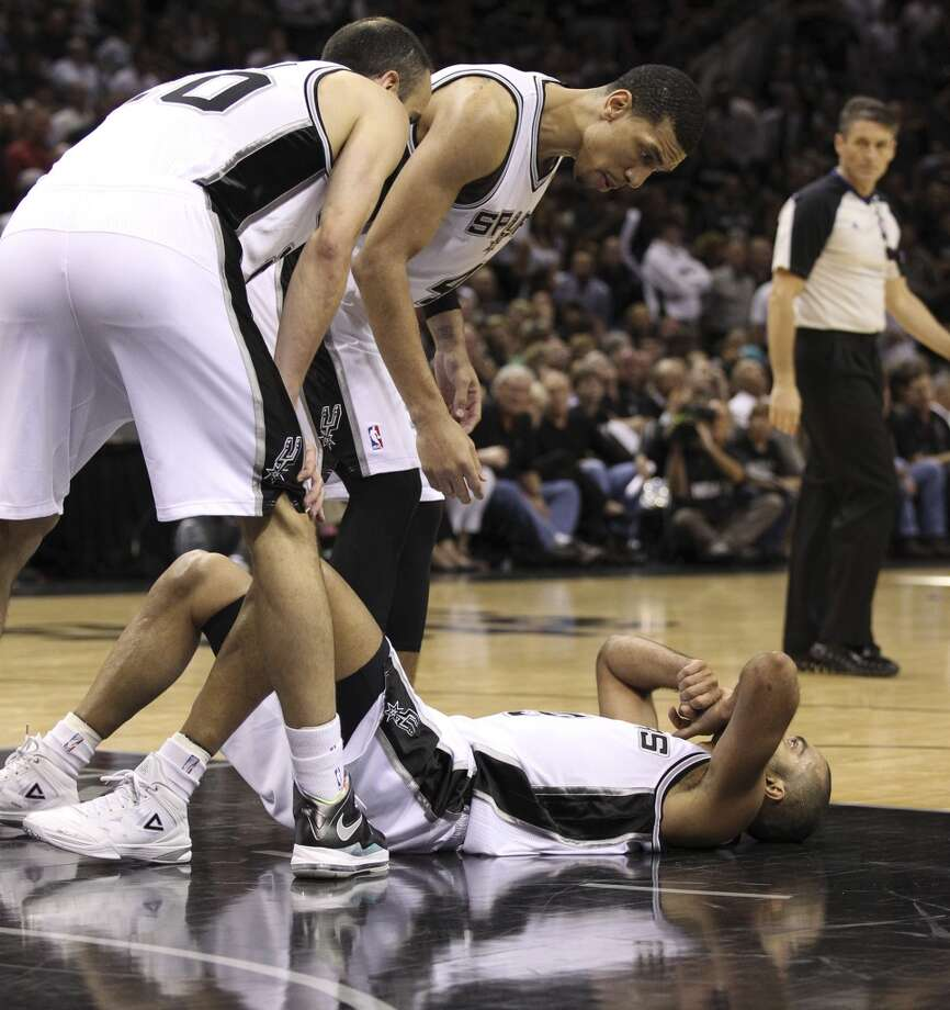 San Antonio Spurs' Tony Parker lies on the floor as teammates San Antonio Spurs' Manu Ginobili, left, and San Antonio Spurs' Danny Green during the second half of Game 4 of the NBA Finals at the AT&T Center on Thursday, June 13, 2013. (Kin Man Hui/San Antonio Express-News)