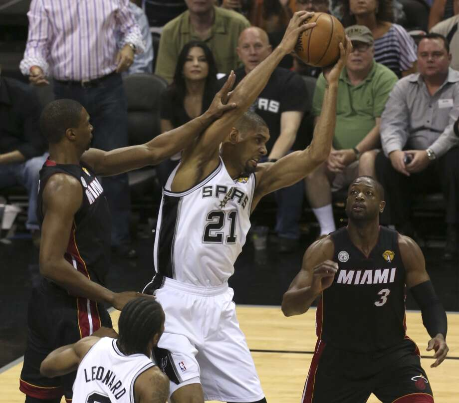 San Antonio Spurs' Tim Duncan grabs the ball from between Miami Heat's Chris Bosh, left, and Miami Heat's Dwyane Wade, right, during the first half of Game 4 of the NBA Finals at the AT&T Center on Thur., June 13, 2013. (Jerry Lara/San Antonio Express-News)