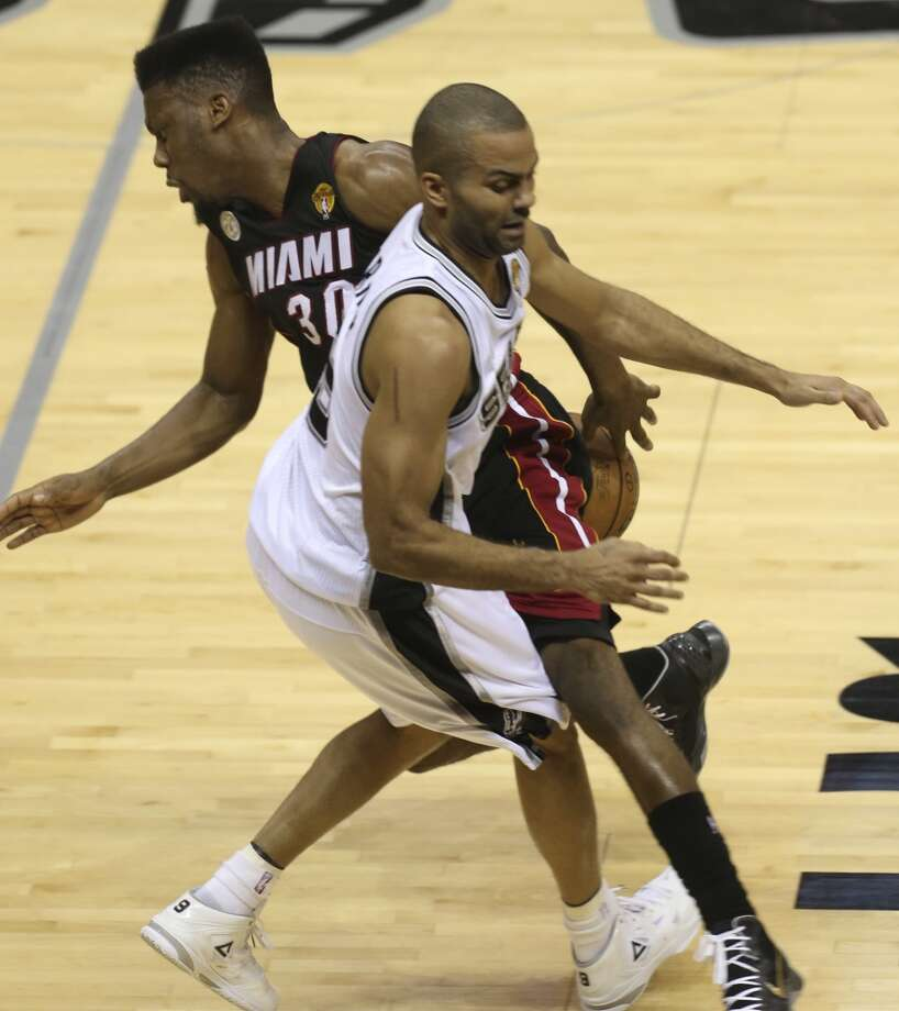 San Antonio Spurs' Tony Parker and Miami Heat's Norris Cole collide during the first half of Game 4 of the NBA Finals at the AT&T Center on Thur., June 13, 2013. (Jerry Lara/San Antonio Express-News)