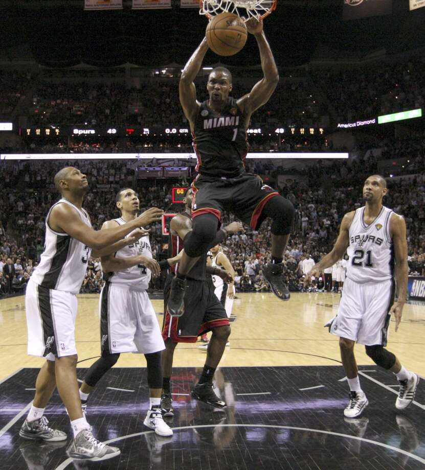 Miami Heat's Chris Bosh dunks over San Antonio Spurs' Boris Diaw, Danny Green, and Tim Duncan during the first half of Game 4 of the NBA Finals at the AT&T Center on Thur., June 13, 2013. (Jerry Lara/San Antonio Express-News)