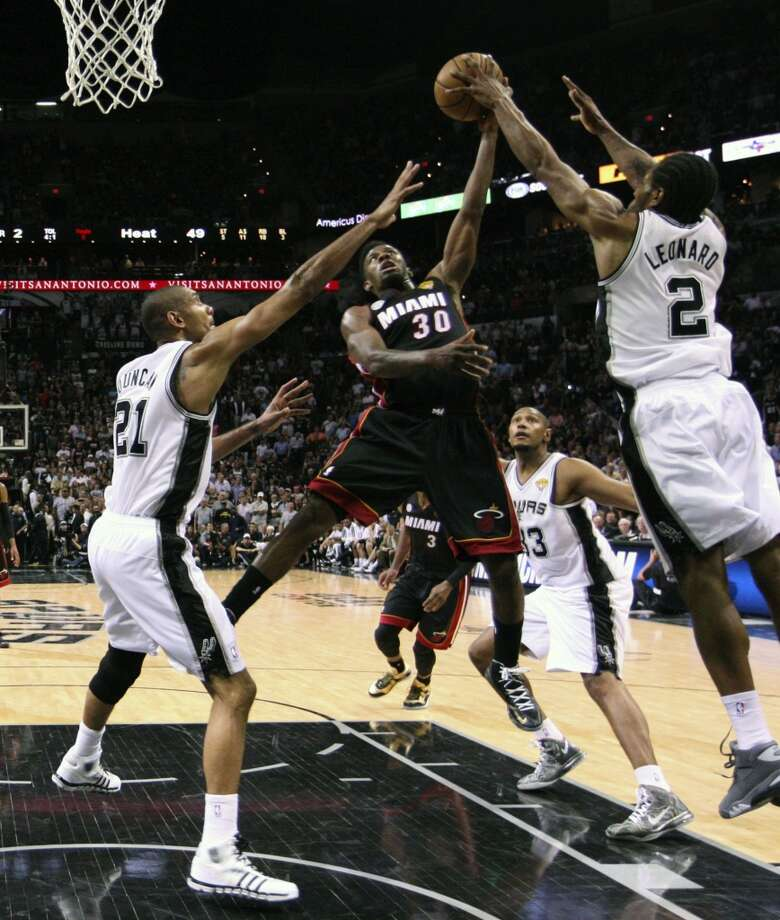 Miami Heat's Norris Cole shoots between San Antonio Spurs' Tim Duncan, Boris Diaw, and Kawhi Leonard during the first half of Game 4 of the NBA Finals at the AT&T Center on Thur., June 13, 2013. (Jerry Lara/San Antonio Express-News)