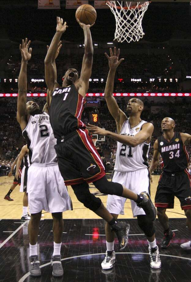 Miami Heat's Chris Bosh shoots between San Antonio Spurs' Kawhi Leonard and Tim Duncan during the first half of Game 4 of the NBA Finals at the AT&T Center on Thur., June 13, 2013. (Jerry Lara/San Antonio Express-News)