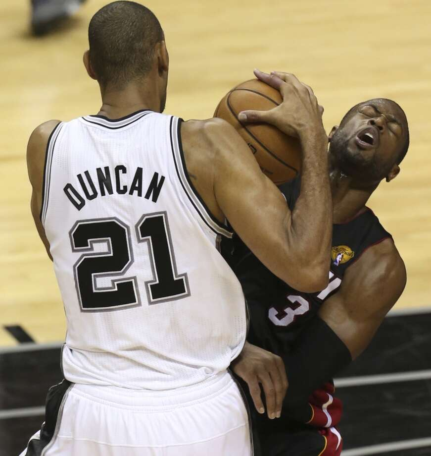 San Antonio Spurs' Tim Duncan collides with Miami Heat's Dwyane Wade during the first half of Game 4 of the NBA Finals at the AT&T Center on Thur., June 13, 2013. (Jerry Lara/San Antonio Express-News)