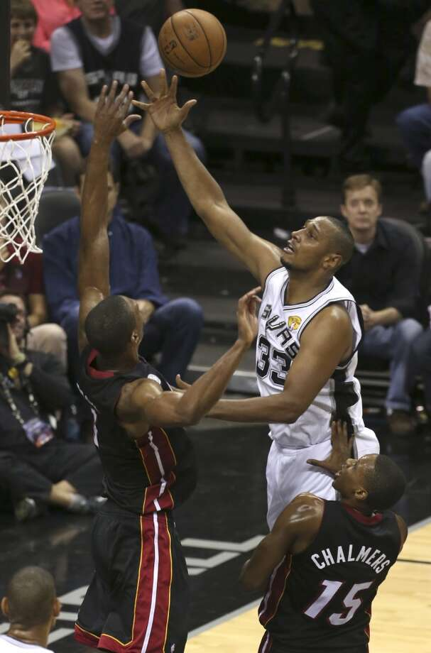 San Antonio Spurs' Boris Diaw shoots over Miami Heat's Chris Bosh and Mario Chalmers during the second half of Game 4 of the NBA Finals at the AT&T Center on Thur., June 13, 2013. (Jerry Lara/San Antonio Express-News)