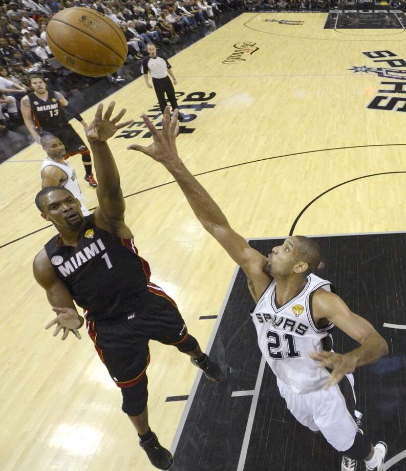 Chris Bosh shoots over Tim Duncan during the first half. Photo: Derick E. Hingle, Associated Press