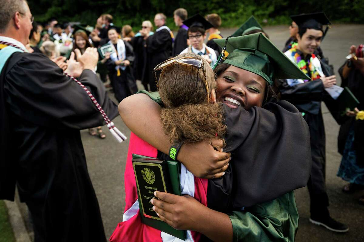 With diplomas in hand, students tearfully embrace friends and faculty following Franklin High School's graduation ceremony Thursday, June 13, 2013, at Memorial Stadium in Seattle.