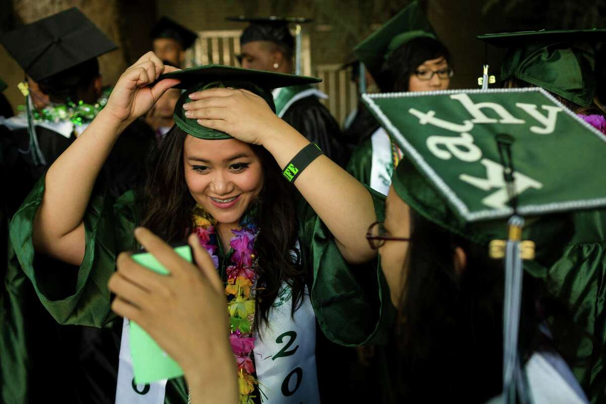 Claire Dang, center, fixes her hat just so in the reflection of Kathy Dinh's phone, right, before Franklin High School's graduation ceremony Thursday, June 13, 2013, at Memorial Stadium in Seattle.