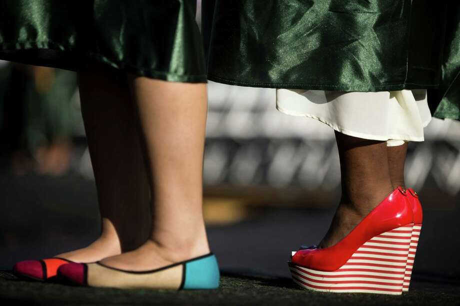 While some opted for tennis shoes to match the gowns, some young women spiced up the green outfits with colorful shoes at Franklin High School's graduation ceremony Thursday, June 13, 2013, at Memorial Stadium in Seattle. Photo: JORDAN STEAD, SEATTLEPI.COM / SEATTLEPI.COM