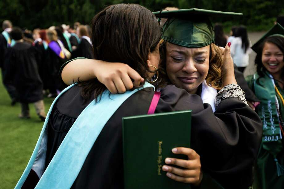 With diploma in hand, Kendra Ames, right, tearfully embraces a faculty member following Franklin High School's graduation ceremony Thursday, June 13, 2013, at Memorial Stadium in Seattle. Photo: JORDAN STEAD, SEATTLEPI.COM / SEATTLEPI.COM