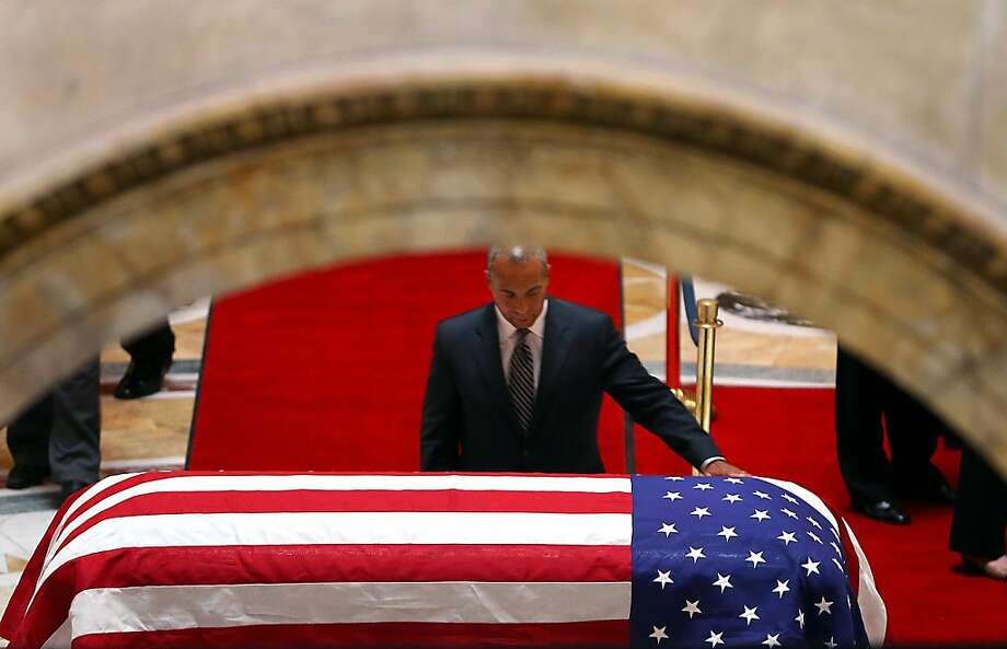 Gov. Deval Patrick places his hand on the casket in Memorial Hall as he led the line of dignitaries to visit the casket of former Gov. Paul Cellucci on Thursday, June 13, 2013 in Boston.  Massachusetts political figures of both parties paid glowing tribute to Cellucci, a Republican who never lost an election in a Democratic-leaning state, in the building where he spent nearly a quarter of a century in public life. Cellucci, 65, died Saturday of complications from ALS, also known as Lou Gehrig's disease. (AP Photo/The Boston Globe, John Tlumacki, Pool) Photo: John Tlumacki, Associated Press