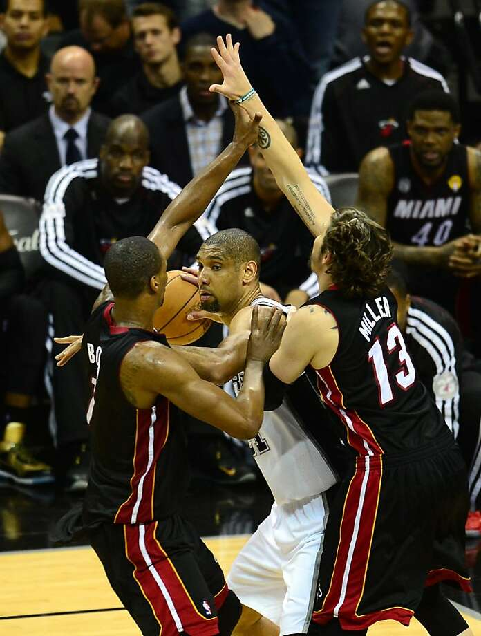 Tim Duncan (C) of the San Antonio Spurs looks to pass under pressure from tough defense of Chris Bosh (L) and Mike Miller (R) of the Miami Heat during game 4 of the NBA finals on June 13, 2013 in San Antonio, Texas, where the Heat defeated the Spurs 109-93 to even the series 2-2.  AFP PHOTO/Frederic J. BROWNFREDERIC J. BROWN/AFP/Getty Images Photo: Frederic J. Brown, AFP/Getty Images