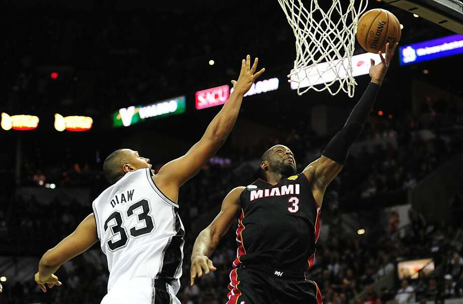 Dwayne Wade (R) of the Miami Heat drives to the basket under pressure from Boris Diaw (L) of the San Antonio Spurs during game 4 of the NBA finals on June 13, 2013 in San Antonio, Texas, where the Heat defeated the Spurs 109-93 to even the series 2-2.  AFP PHOTO/Frederic J. BROWNFREDERIC J. BROWN/AFP/Getty Images Photo: Frederic J. Brown, AFP/Getty Images