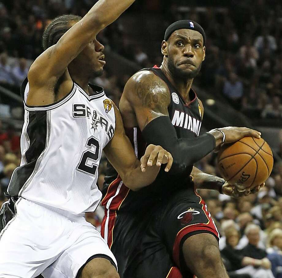 The Miami Heat's LeBron James drives against the San Antonio Spurs' Kawhi Leonard, left, in the first quarter of Game 4 of the NBA Finals at the AT&T Center in San Antonio, Texas, on Thursday, June 13, 2013. (Al Diaz/Miami Herald/MCT) Photo: Al Diaz, McClatchy-Tribune News Service