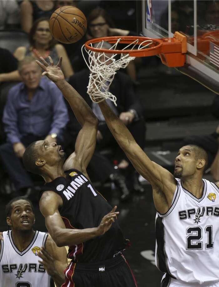 Miami Heat's Chris Bosh shoots over San Antonio Spurs' Tim Duncan, right, and Kawhi Leonard during the second half of Game 4 of the NBA Finals at the AT&T Center on Thur., June 13, 2013. (Jerry Lara/San Antonio Express-News)