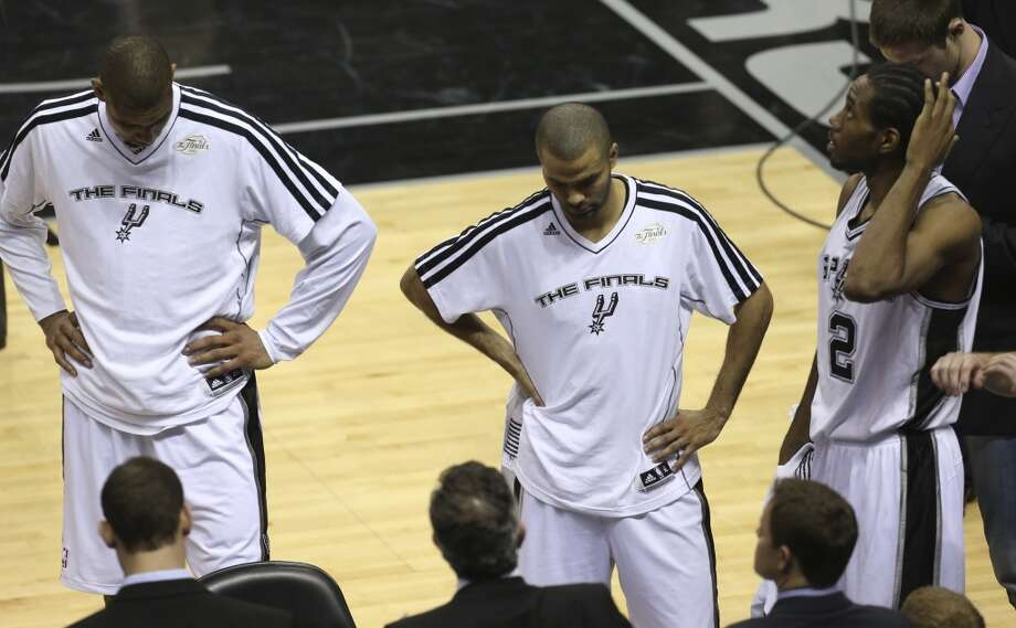 San Antonio Spurs' Tim Duncan, Tony Parker and Kawhi Leonard react near the end of the end of during Game 4 of the NBA Finals at the AT&T Center on Thur., June 13, 2013. (Jerry Lara/San Antonio Express-News)