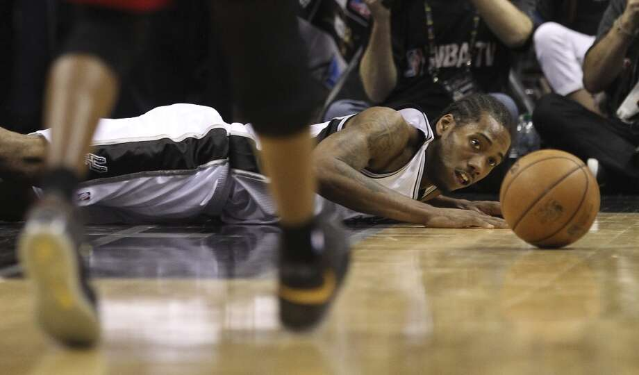 San Antonio Spurs' Kawhi Leonard falls to the floor for a rebound against the Miami Heat during the second half of Game 4 of the NBA Finals at the AT&T Center on Thursday, June 13, 2013. Heat defeat the Spurs, 109-93. (Kin Man Hui/San Antonio Express-News)