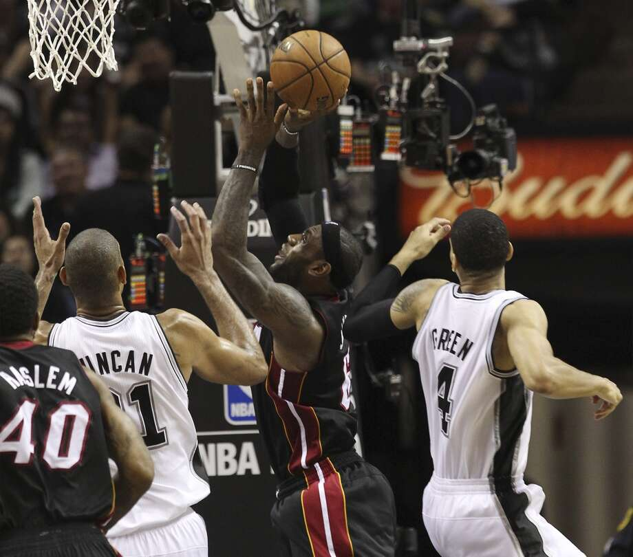 Miami Heat's LeBron James attempts a shot between San Antonio Spurs' Tim Duncan and Danny Green during the second half of Game 4 of the NBA Finals at the AT&T Center on Thursday, June 13, 2013. (Kin Man Hui/San Antonio Express-News)