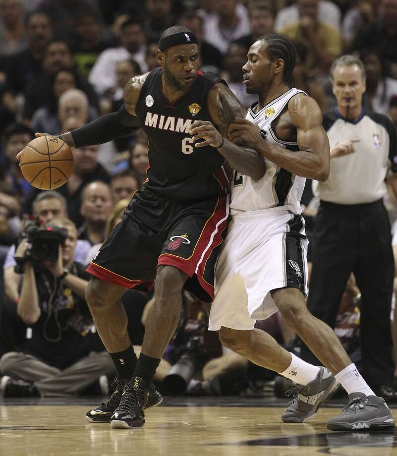 Miami Heat's LeBron James gets defended by San Antonio Spurs' Kawhi Leonard during the first half of Game 4 of the NBA Finals at the AT&T Center on Thursday, June 13, 2013. (Kin Man Hui/San Antonio Express-News)