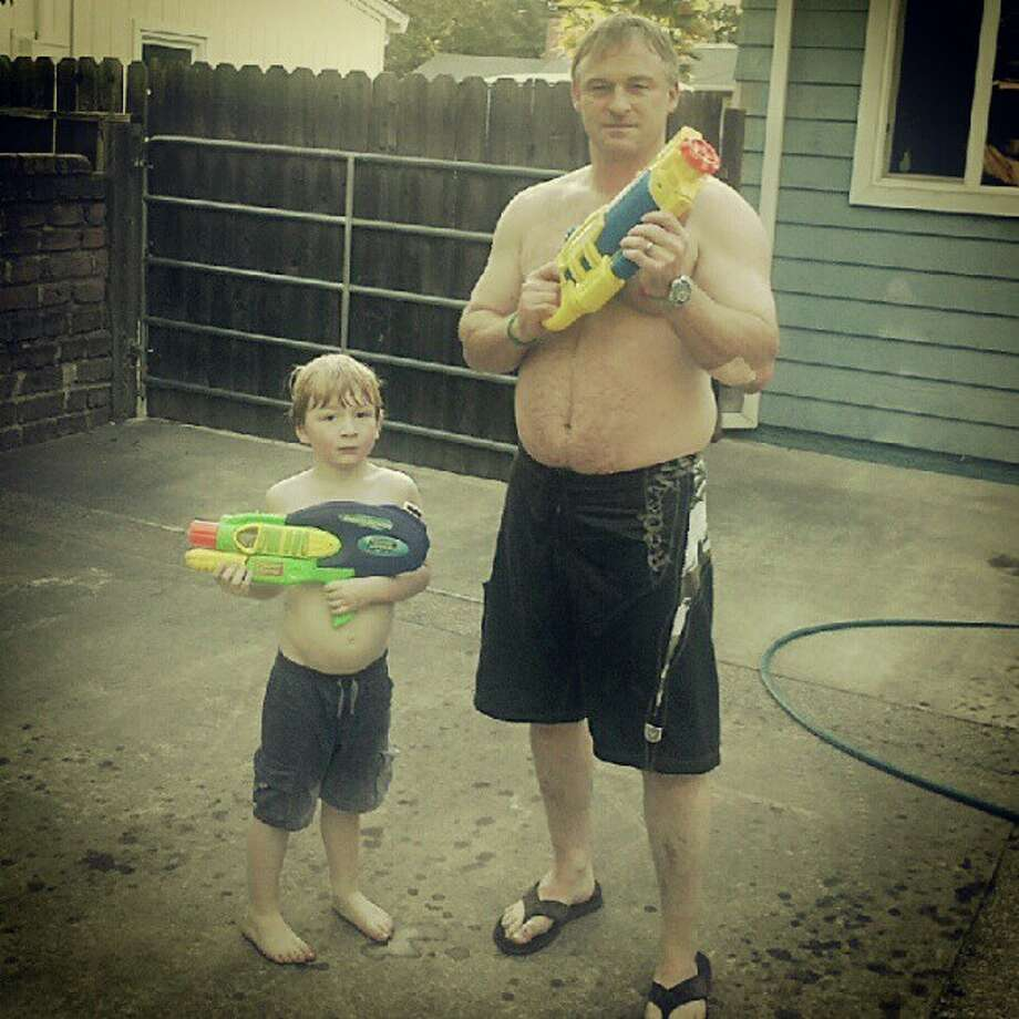 This father and his son shoot water guns together.