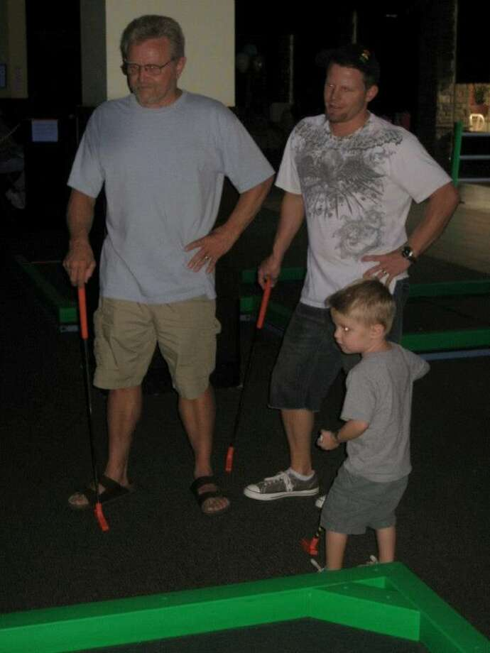 Some fathers and sons play miniature golf together. Photo: Dnollet