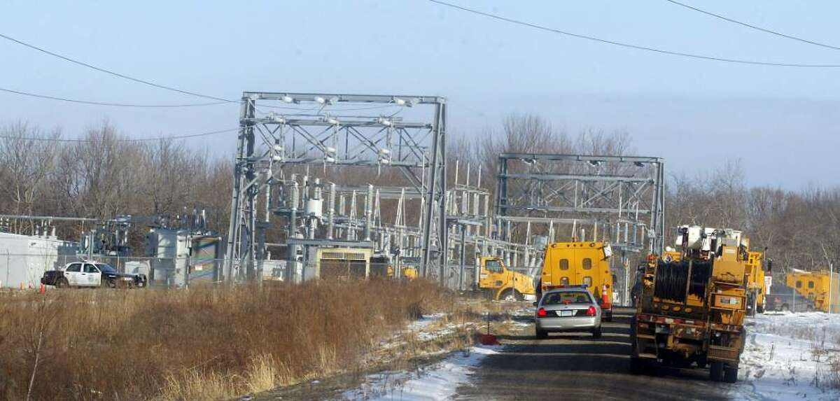 While the NTSB investigates the crash of a single engined experimental plane near runway 18/36 at Oxford Airport, Oxford and State Police monitor the access road to the crash site. Connecticut Light and Power vehicles wait to to repair a power substation and transmission lines damaged in the crash. Thursday, Jan. 14, 2010.