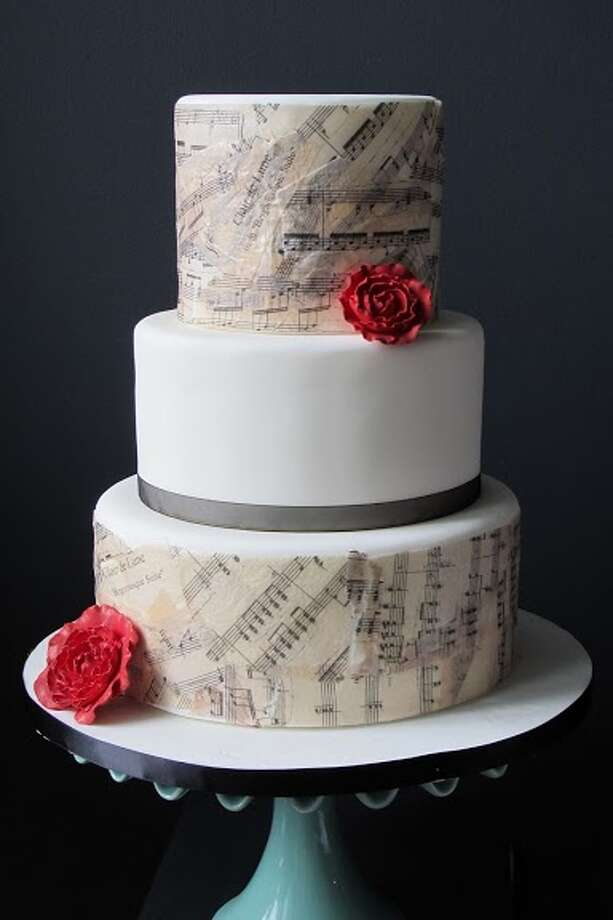 Fondant with edible rise paper printed with sheet music and red sugar flowers by Beyond Buttercream.