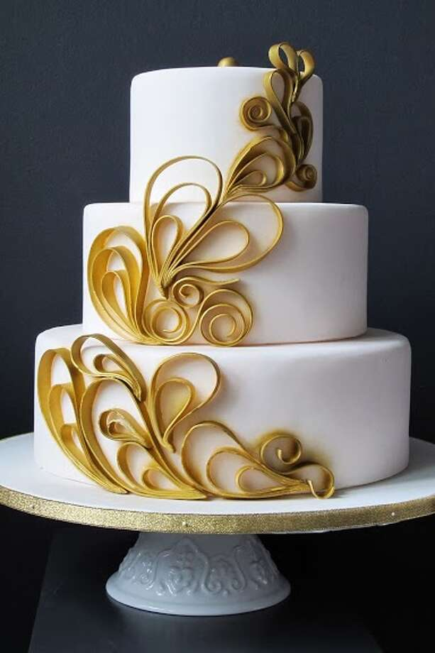 White fondant with gold fondant ribbons by Beyond Buttercream.