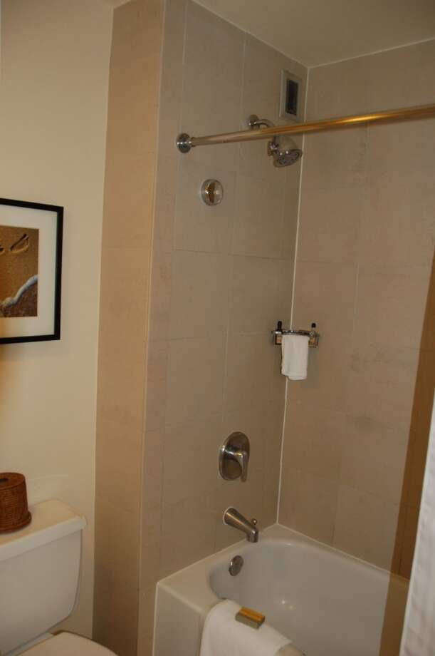 The marble-lined shower/tub and toilet are separated from the vanity area by a door, for privacy.