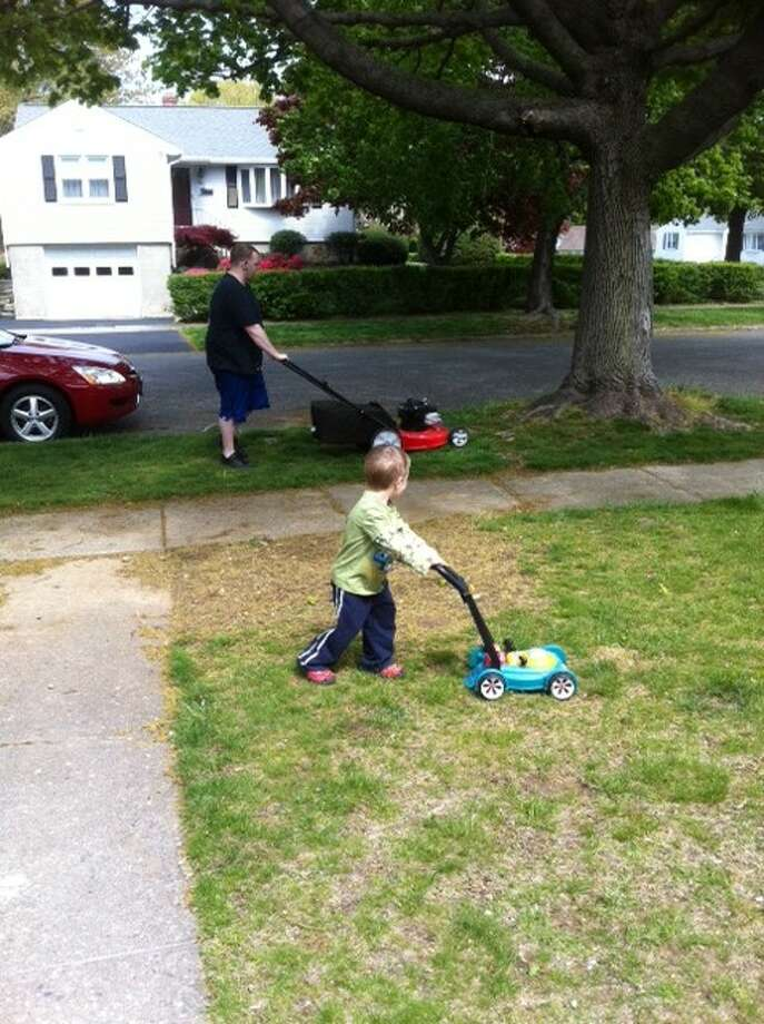 Some fathers and sons mow the lawn together. Photo: Rac12157