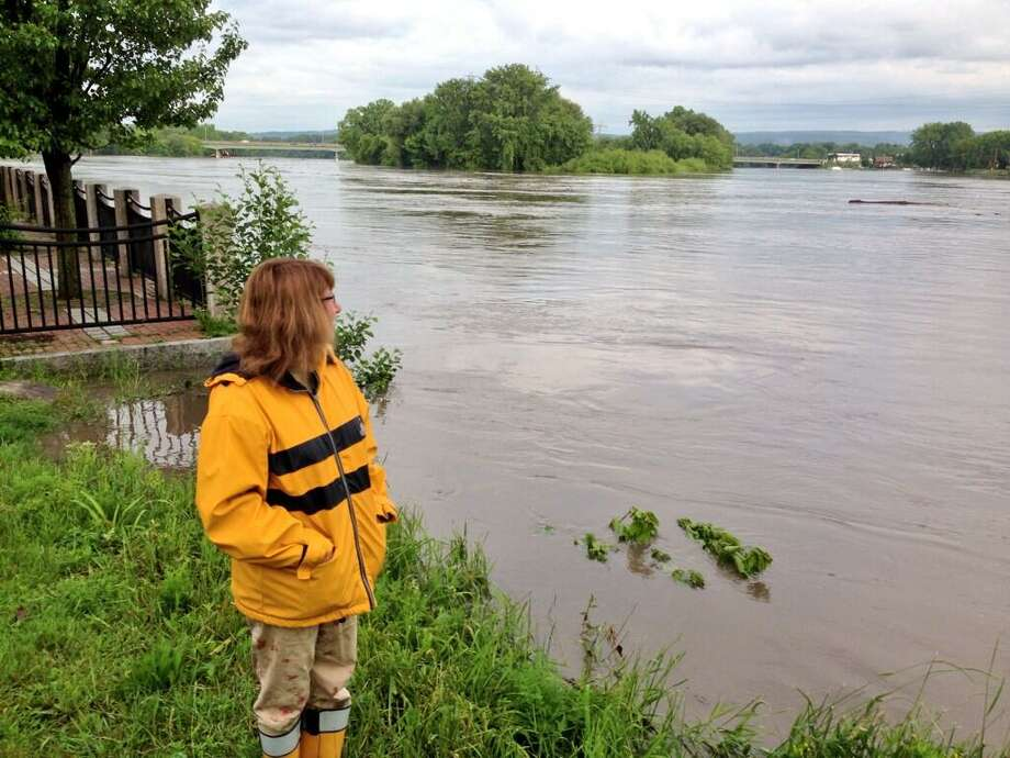 Betsy Meyer, a resident of North Street in Schenectady's Stockade neighborhood watches the level of the Mohawk River in Riverside Park. The National Weather Service does not expect major flooding to hit the area as it dries out from Thursday's heavy rains. (Skip Dickstein / Times Union)