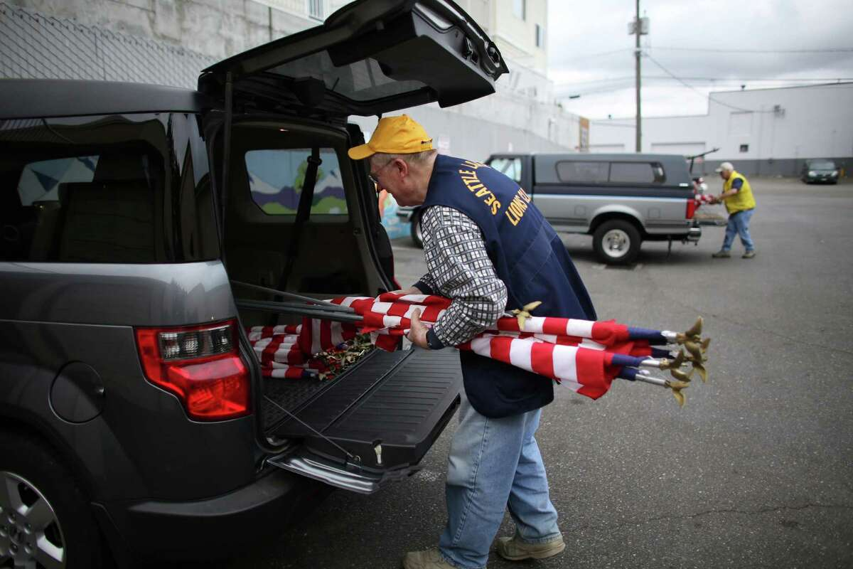 Tom Lentz of the Lake City Lions Club gathers flags as a crew of Lions Club members head out to place flags on businesses in north Seattle and Shoreline on Flag Day, Friday, June 14, 2013.