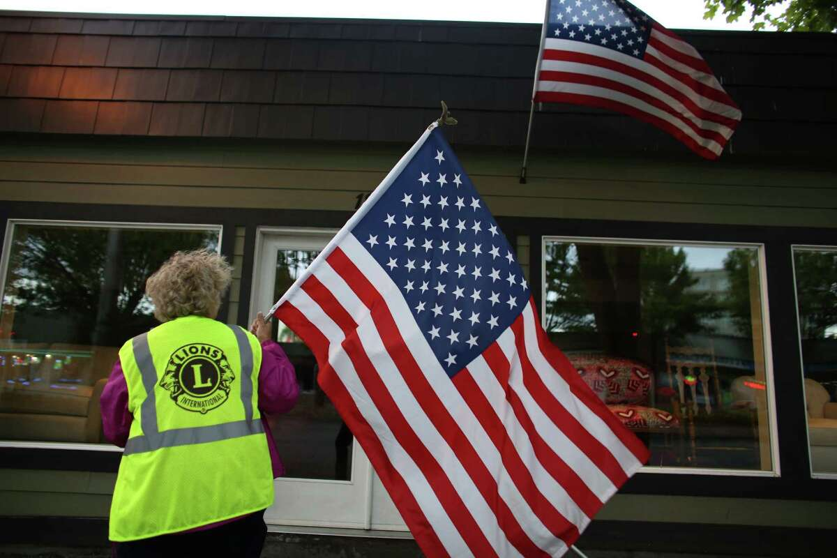 Susan Potemkin of the Lake City Lions Club prepares to hang a flag as a crew of Lions Club members place flags on businesses in north Seattle and Shoreline on Flag Day, Friday, June 14, 2013.