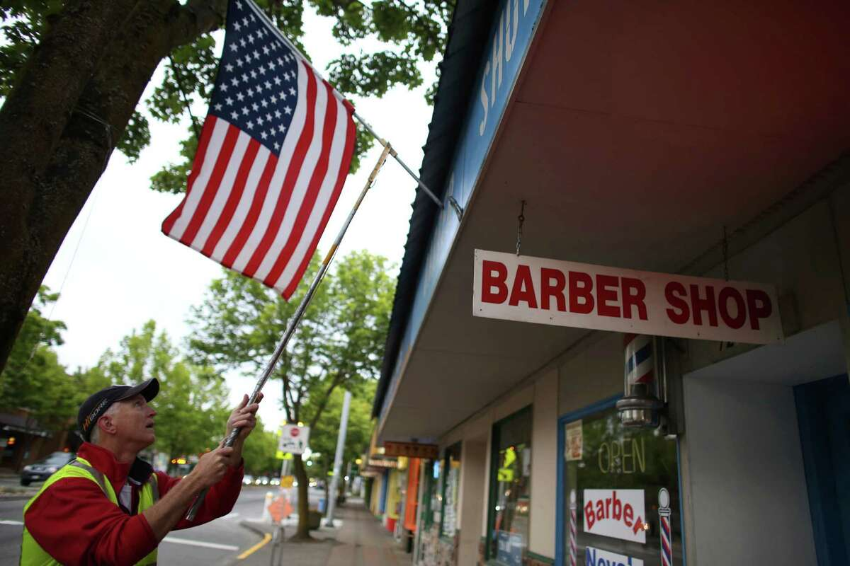 Lake City Lions Club member Randy Taylor hangs a flag as a crew of Lions Club members place flags on businesses in north Seattle and Shoreline on Flag Day, Friday, June 14, 2013.