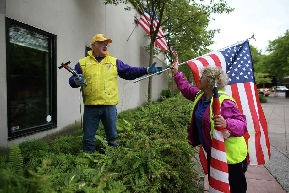 Lake City Lions Club members Bob Brown and Susan Potemkin hang flags as a crew of Lions Club members place flags on businesses in north Seattle and Shoreline on Flag Day, Friday, June 14, 2013. Photo: JOSHUA TRUJILLO, SEATTLEPI.COM / SEATTLEPI.COM