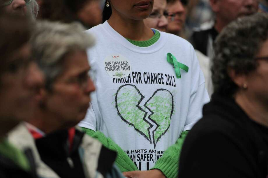 A spectator wears Sandy Hook stickers and ribbons at the six-month anniversary remembrance ceremony of the Sandy Hook Elementary School shooting at Edmond Town Hall in Newtown, Conn. on Friday, June 14, 2013.  Politicians and families of victims spoke at the event, followed by a reading of names of the 6,003 vicitims of U.S. gun violence since the Dec. 14 shooting at Sandy Hook. Photo: Tyler Sizemore / The News-Times