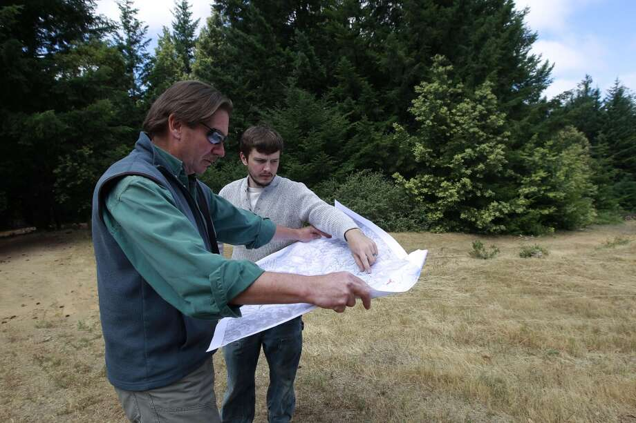 Chris Kelly, (left),  the California Director and Brian Pickett, a forester,  for The Conservation Fund consult over a map of the Preservation Ranch property  near Annapolis, Calif.